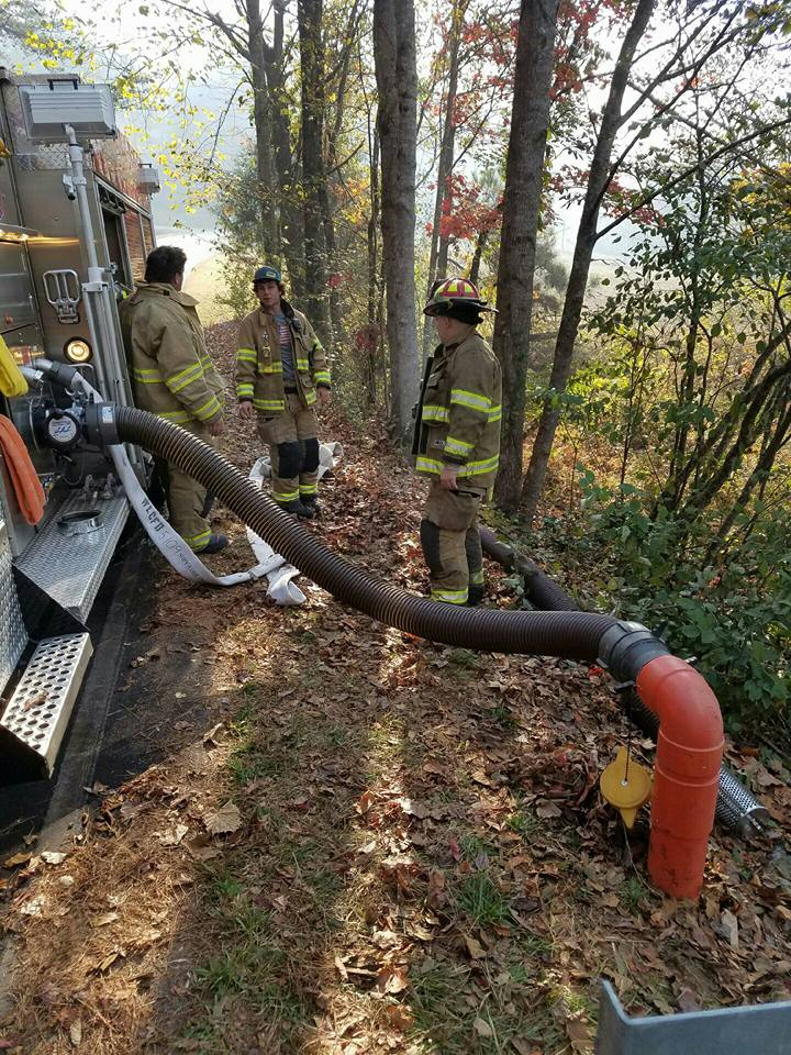 Laurens County firefighters take a short breather while they fill their engine with water at Pinnacle Mountain on Wednesday. Nine firefighters from four local departments are assisting in the multi-state effort to get the 3,000-acre wildfire under control.